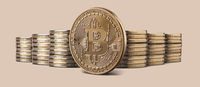 Cryptocurrency physical bitcoin gold coin and stacks of coins on backgound