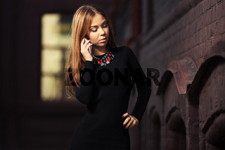 Young fashion woman in black dress calling on cell phone