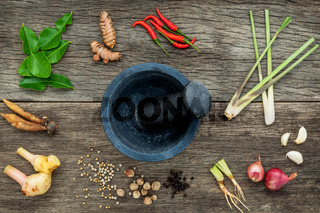 Assortment of Thai food Cooking ingredients and spice red curry paste ingredient of thai popular food on rustic wooden background. Spices ingredients chilli ,pepper, garlic and Kaffir lime leaves .