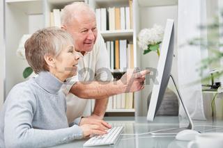 Senioren Paar schaut auf Monitor