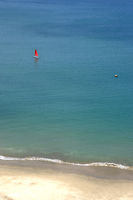 Small yacht under a scarlet sail along the blue sea in Salinas Bay, Ecuador