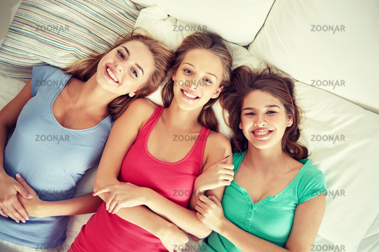 happy young women in bed at home pajama party