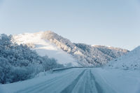 Snow road and car tracks on the road in the winter in the North Caucasus. Snow-covered trees and mountains. The concept of winter travel by car
