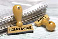 compliance and legal printed on stamps laying on stack of forms