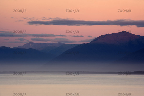 Daemmerlicht, Meer und Berge in der Gegend um Jackson Bay nach Sonnenuntergang. Das Daemmerlicht wirft unglaubliche Rot- und Rosatoene an den Himmel, Jackson Bay, Haast, Suedinsel, Neuseeland, Twilight, ocean and mountains around Jackson Bay at twilight a