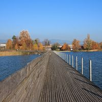 Boardwalk connecting Rapperswil and Hurden, Switzerland. Blue lake Obersee.
