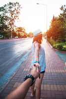 Girl holding a hand man on the street