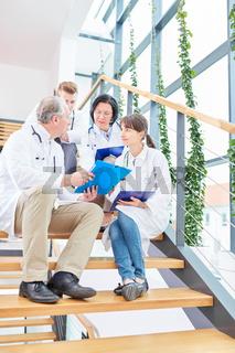 Chefarzt bespricht mit seinem Team eine Patientenakte