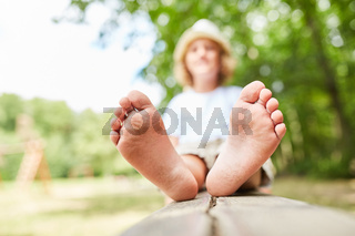 Junge sitzt barfuß auf einer Parkbank