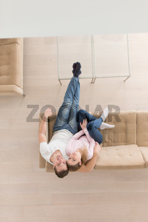 Young couple on the sofa watching television top view