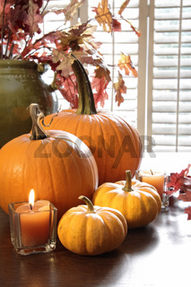 Pumpkins and gourds with candle near window