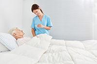Krankenschwester beim Fieber messen einer Seniorin