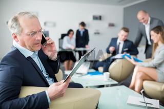 Älterer Manager telefoniert mit Smartphone