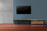Led tv on dark blue wall with wooden furniture in empty living room