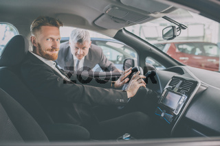 Vehicle dealer showing new car to a handsome man.