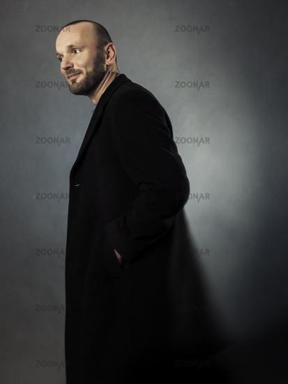 bearded man in a black coat