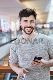 Junger Mann mit Smartphone beim Shopping