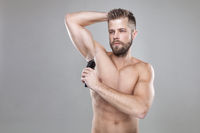 Handsome young bearded man with a trimmer shaving off body hair