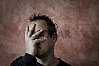 mann mit dreitagebart und wirrem haar hält sich die hand vors gesicht