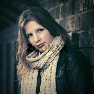 Young fashion girl with long hairs next to brick wall