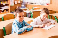 two boys are sitting at the desk on the lesson