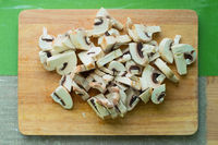 Close-up of chopped mushrooms lying on a wooden cutting board on a green kitchen table.