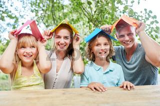 Familie mit Papier Dächern auf dem Kopf