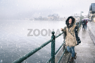 Woman on lakeshore while snowing