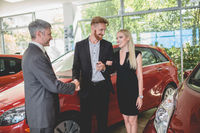 Happy couple at auto showroom, shaking hands with dealer, taking keys from new car