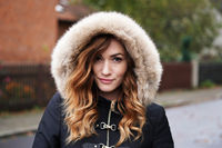 young woman wearing winter coat with fake fur hood outdoors