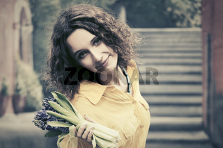 Happy young fashion woman with bouquet of flowers walking in city street