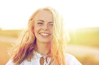 close up of happy young woman in white outdoors