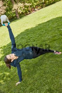 Frau mit Kettlebell beim Fitnesstraining im Park
