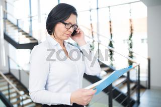Geschäftsfrau mit Klemmbrett und Handy telefoniert