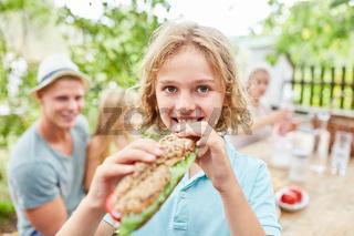 Blonder Junge isst ein frisches Baguette