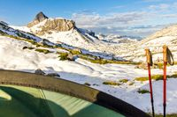 Tent and hiking sticks in snowy mountain landscape. Trekking in Swiss Alps. Hoch Turm, Charetalp, Switzerland.