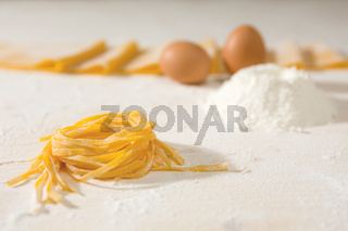 Closeup of fresh uncooked tagliatelle pasta over a table