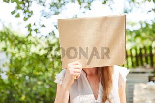 Frau mit Gesicht im Pappkarton