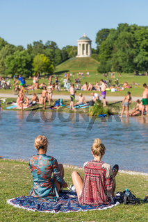 People tanning, swimming and enjoying the summer in Englischer Garten in Munich, Germany.