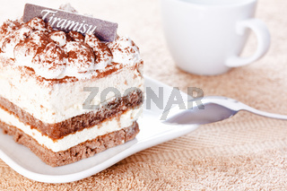Portion of tiramisu dessert served on a white shaped plate and a cup of coffee