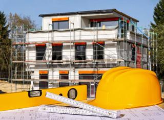 Baustelle mit Helm, Wasserwaage, Zollstock und Bauplänen