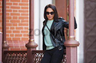 Young fashion woman in black leather jacket leaning on railing