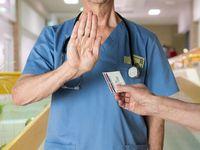 Senior doctor in scrubs refusing Medicare Card