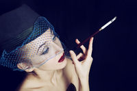 Portrait of a young beautiful woman dressed in a hat with a veil smoking a cigarette. Photo in retro style on a black background