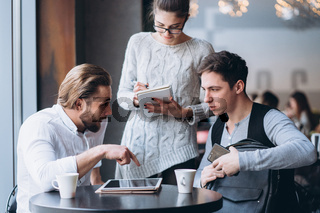 Three Businesspeople Working In cafe