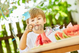 Junge steckt Fähnchen als Deko auf Wassermelonen