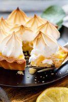 Piece of lemon tart on a fork closeup.