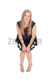 Happy woman in a short black dress bending