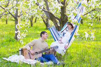 Pregnant couple in blooming garden at the picnic