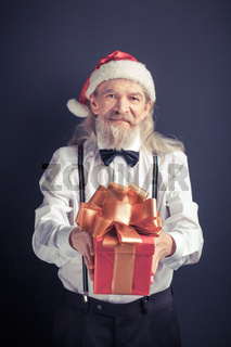 Santa Claus in white shirt with gift box in hands.